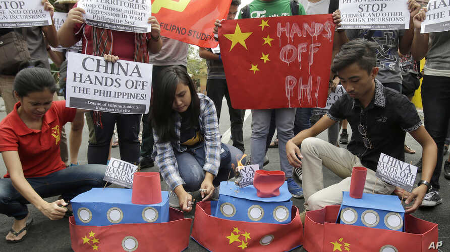 FILE - Filipino student activists set fire mock Chinese ships to protest recent island-building and alleged militarization by China off the disputed Spratlys group of islands in the South China Sea, in Manila, March 3, 2016.
