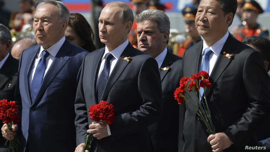 Russian President Vladimir Putin (C), Kazakhstan's President Nursultan Nazarbayev (L) and China's President Xi Jinping take part in a wreath laying ceremony at the Tomb of the Unknown Soldier on the Victory Day by the Kremlin walls in central Moscow,
