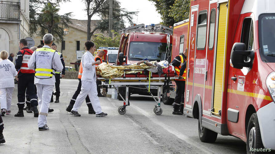 Rescue workers carry a injured person on a stretcher during rescue operations near the site where a coach carrying members of an elderly people's club collided with a truck outside Puisseguin near Bordeaux, western France, October 23, 2015.