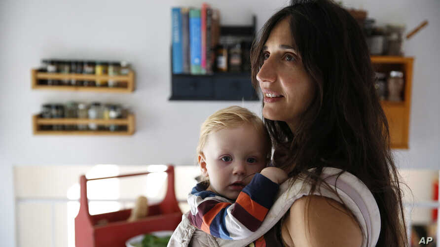 FILE - Vegan mother Fulvia Serra carries her 1-year-old baby, Sebastiano, at home in Fort Collins, Colo., Oct. 20, 2016. Serra, originally from Italy, and her husband, Scott, are raising their son vegan.