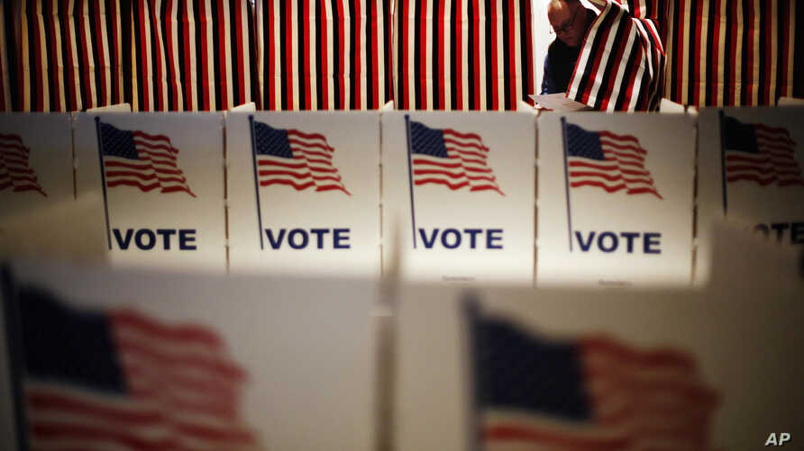 Jim Smith steps out of a voting booth after marking his ballot at a polling site for the New Hampshire primary, Feb. 9, 2016, in Nashua, N.H.
