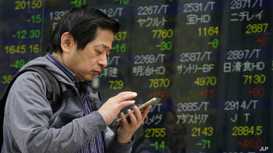 A man uses smartphone in front of an electronic stock indicator of a securities firm in Tokyo, March 26, 2018.
