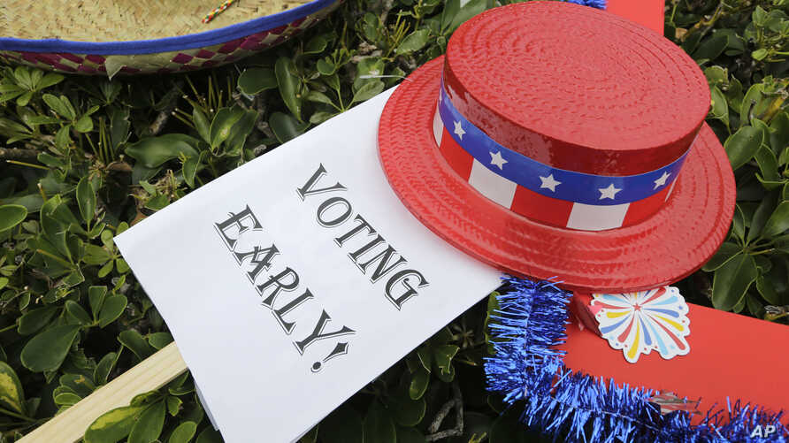 An early voting sign lies on the grass at an early voting celebration outside of Jackson Memorial Hospital, on the first day of early voting in Miami-Dade County for the general election, Oct. 24, 2016, in Miami, Florida.