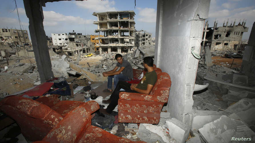 Palestinians return to the remains of their house after the ceasefire was declared, in the east of Gaza City. Aug. 27, 2014.