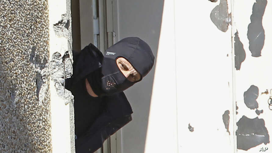 FILE -  A masked policeman searches for clues at terrorist Mohamed Merah's apartment building in Toulouse, southern France.