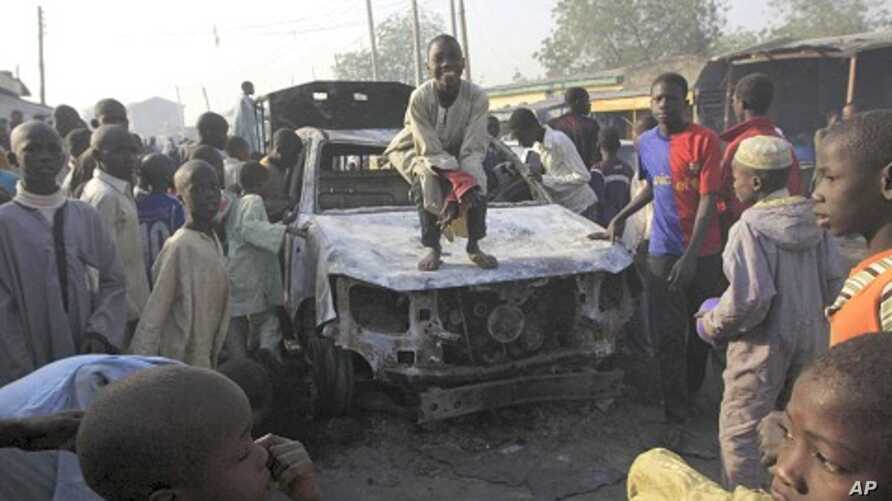 A child stands on a burnt out police truck following an overnight attack at Sheka police station in Kano, Nigeria, January 25, 2012.