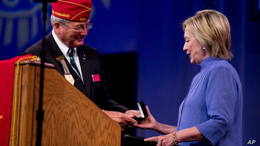 American Legion National Commander Dale Barnett presents an award to Democratic presidential candidate Hillary Clinton after she spoke at the American Legion's 98th Annual Convention at the Duke Energy Convention Center in Cincinnati, Ohio, Aug. 31,