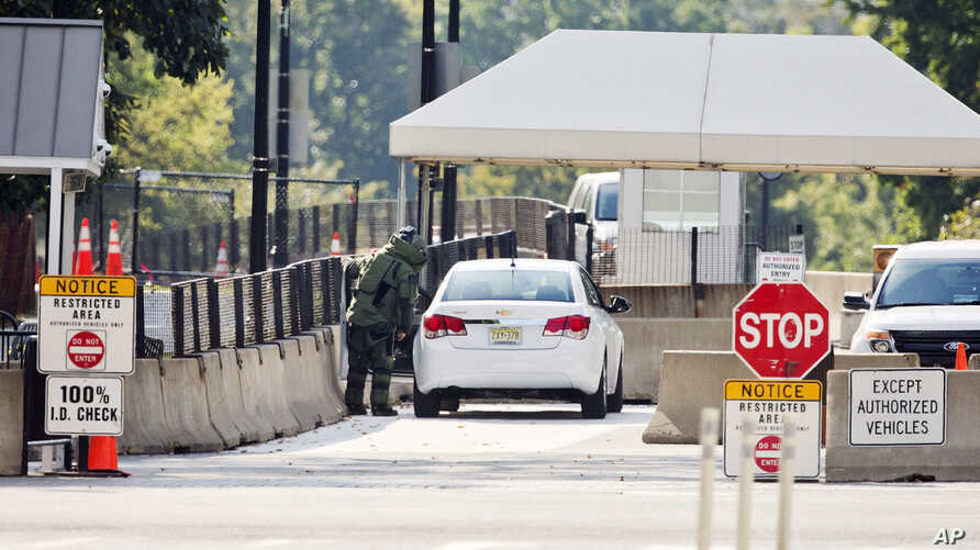 An explosive technician in a bomb suit approaches a vehicle near the entrance to White House in Washington, Sept. 20, 2014.