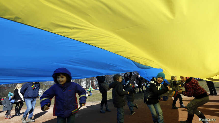 Children play as people hold up a giant Ukrainian flag to protest against the Russian intervention in Ukraine during the celebration of Lithuania's independence in Vilnius, Lithuania, Tuesday March 11, 2014.