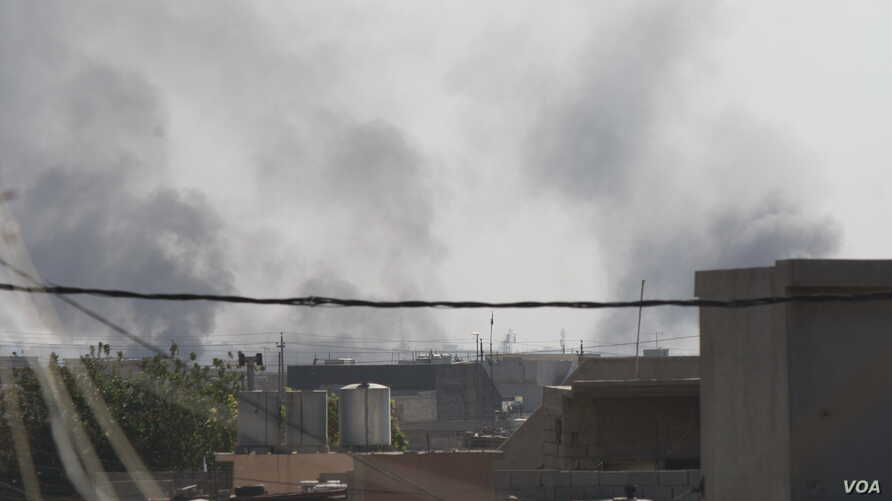 Smoke rises from a large apartment complex as militants exchange fire with Iraqi soldiers in Mosul, Nov. 19, 2016.