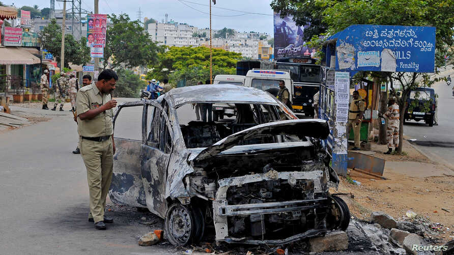 A police officer inspects the charred remains of a car set ablaze in Bengalore, following violent protests after India's Supreme Court ordered Karnataka state to release water from the Cauvery river to the neighbouring state of Tamil Nadu, India, Sep
