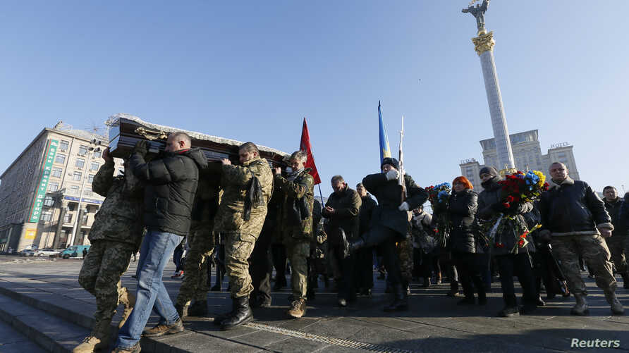 People carry the coffin containing the body of Ukrainian serviceman Volodymyr Andreshkiv, killed while fighting with pro-Russian separatists in eastern Ukraine, during a memorial ceremony at the Independence Square in central Kiev, Ukraine, Dec. 22,
