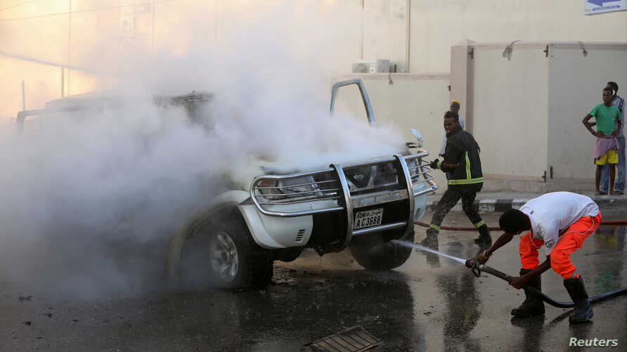 Firefighters attempt to extinguish a burning car after an explosion in Mogadishu, Somalia, Sept. 22, 2018.