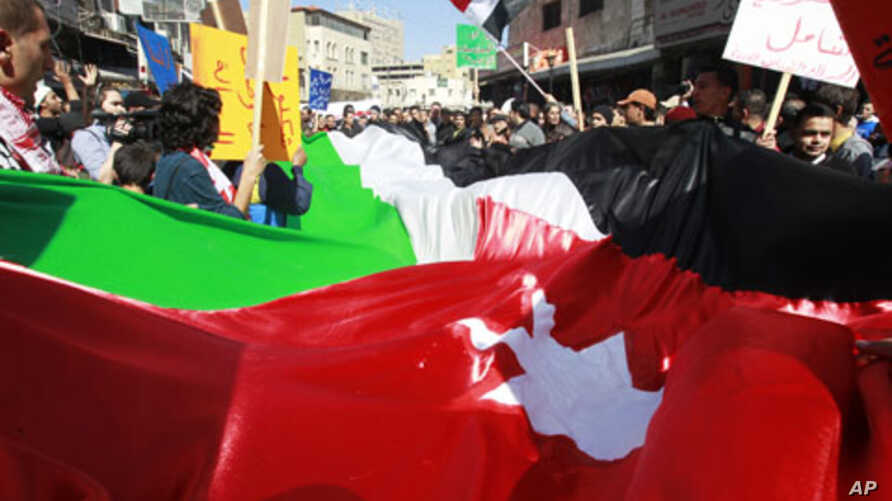Protesters from Jordanian opposition parties carry a giant national flag while shouting anti-government slogans during a demonstration against what they say are worsening economic conditions, after Friday prayers in Amman, February 18, 2011