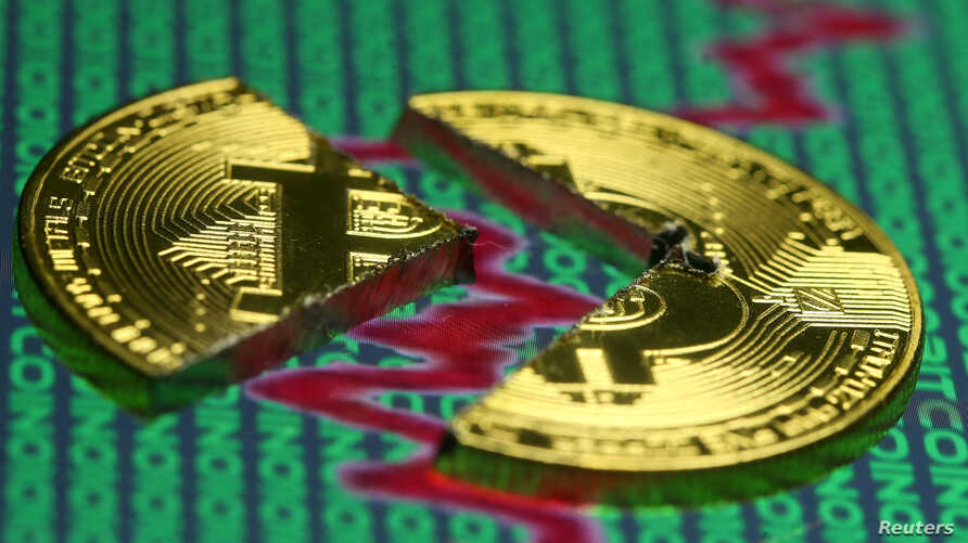 FILE - Broken representation of the Bitcoin virtual currency, placed on a monitor that displays stock graph and binary codes, are seen in this illustration picture, Dec. 21, 2017.