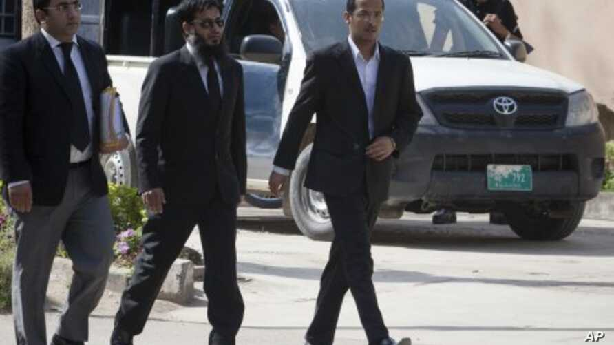 Zakarya Ahmad Al-Fattah (R), brother of Osama bin Laden's youngest widow, Yemen-born Amal Al-Sadeh, arrives with their lawyer Amir Khalil (L) to attend court proceedings at a house where bin Laden's family is believed to be detained in Islamabad Apri