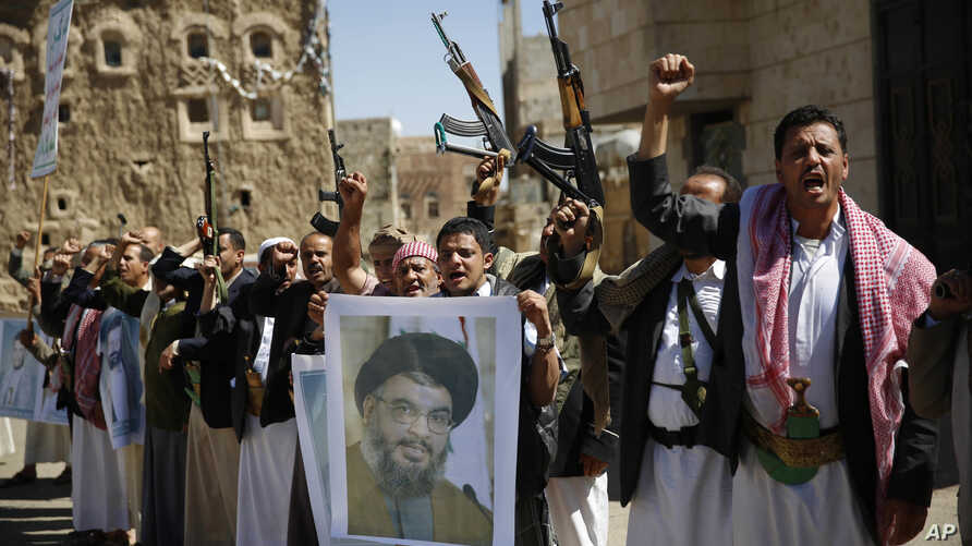 FILE - Shi'ite rebels, known as Houthis, hold a poster of Hezbollah leader Sheikh Hassan Nasrallah during a rally in support of Iranian-backed Hezbollah, in Sana'a, Yemen, March 3, 2016.