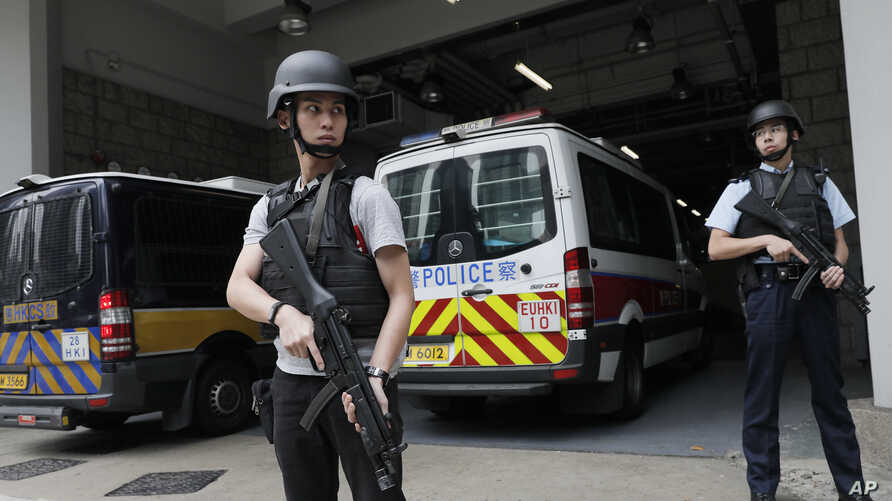 Police officers stand guard next to prison bus which carries British banker Rurik Jutting upon his arrival at the High Court in Hong Kong, Dec. 12, 2017.