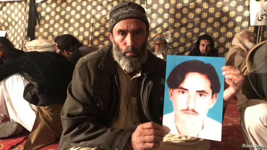 A member of Pakistan's Pashtun community holds a picture of Naqibullah Mehsud, whose extrajudicial killing by Karachi police in January sparked nationwide protests.