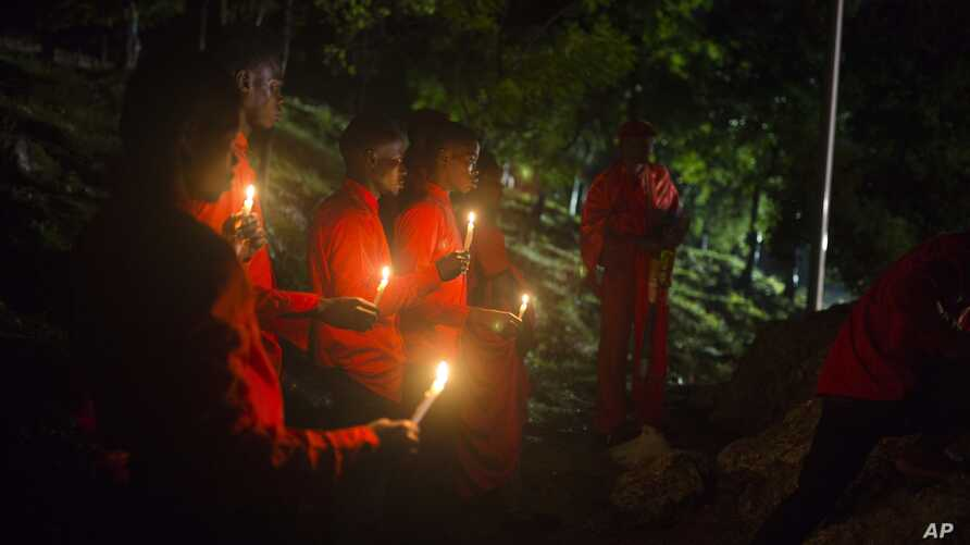 FILE - Faithful hold candles below the Heroes of the Battle of Vertieres monument during a voodoo ceremony one day before the 214th anniversary of the battle that led to Haiti's independence from France in Cap Haitien, Haiti, Nov. 17, 2017.