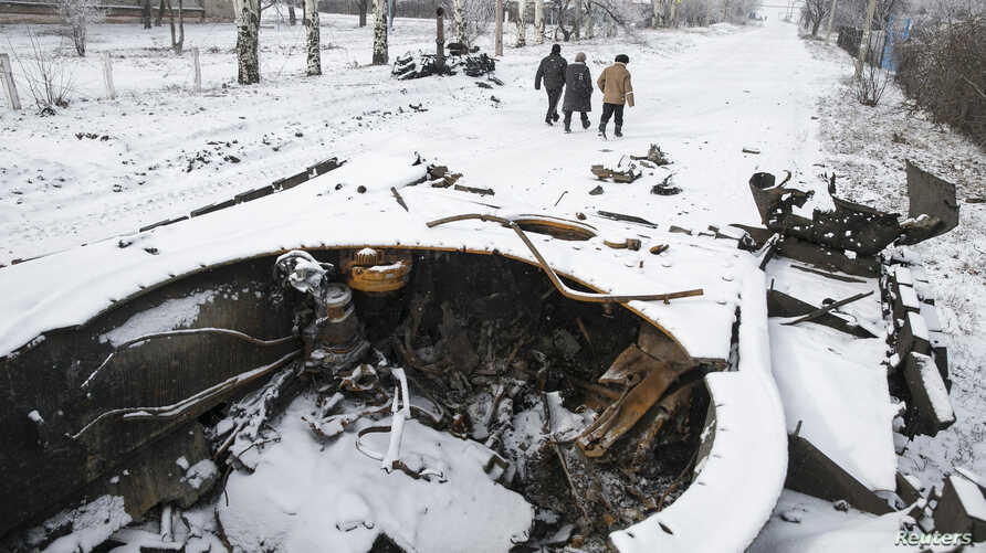 Locals walk past a destroyed Ukrainian army armoured personnel carrier in the town of Vuhlehirsk, about 10 km (6 miles) to the west of Debaltseve, February 16, 2015. Separatists are keeping up attacks on the strategic railway junction of Debaltseve d...