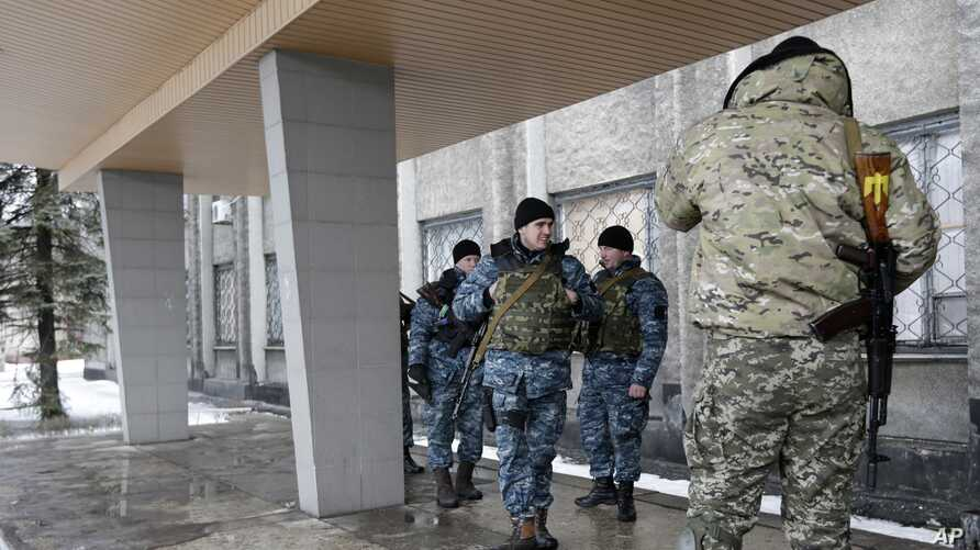 Ukrainian soldiers stands outside of city council building in the town of Debaltseve, Ukraine, Saturday, Jan. 31, 2015.