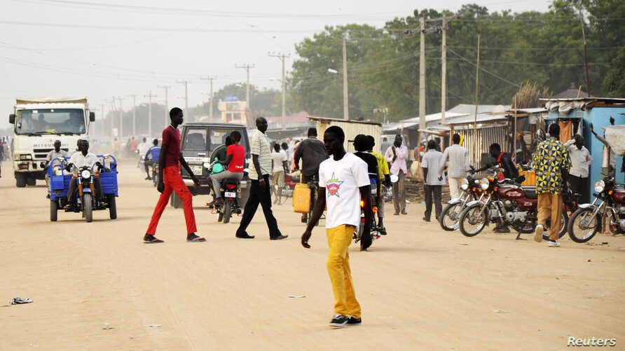 South Sudanese residents walk along a street of Bor, in Jonglei state. Around 1 million children in South Sudan have been forced to flee their homes since conflict erupted a year ago, some are surviving on waterlily roots, and there may be famine nex