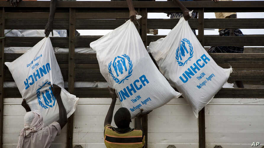 FILE - Workers unload sacks of UNHCR aid supplies at the Al Adala settlement for internally displaced people in Mogadishu,Aug.13, 201.