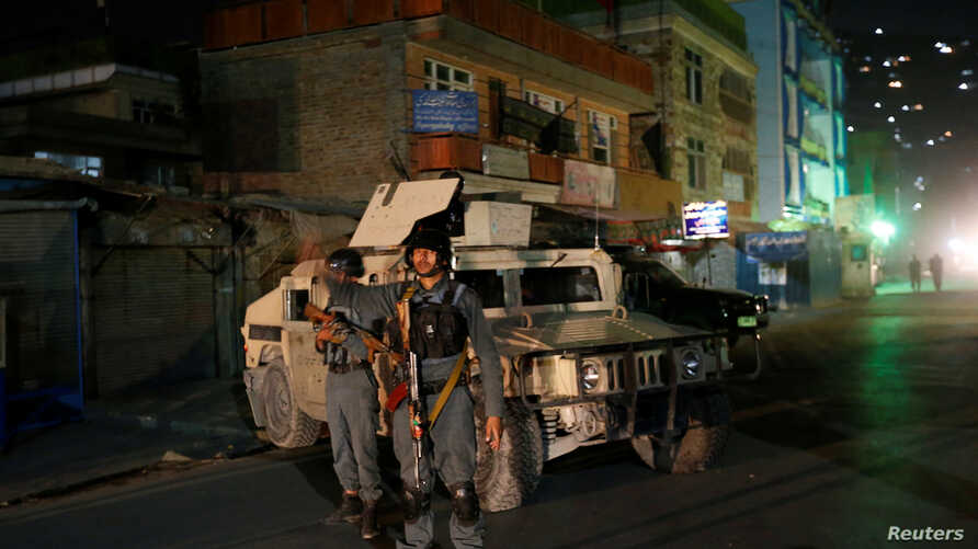 Afghan policemen stand guard near the site of an attack on a shrine in Kabul, Afghanistan October 11, 2016.