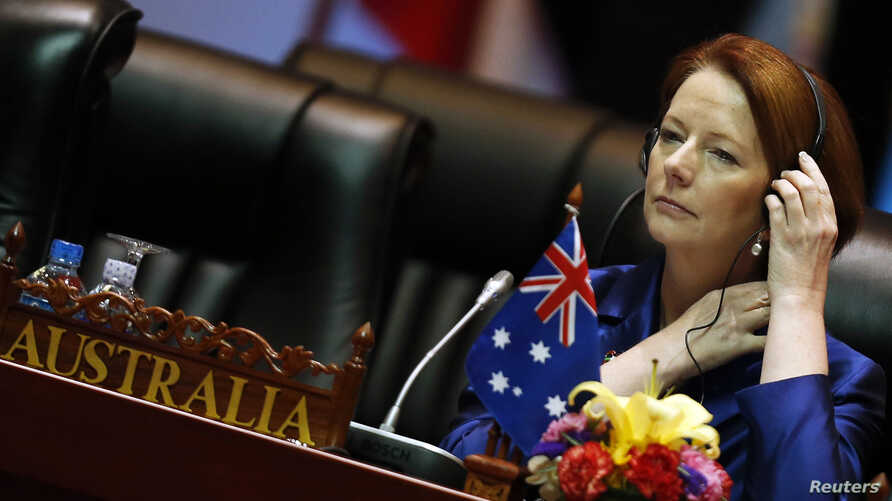 Australia's Prime Minister Julia Gillard adjusts her headphones at the start of a plenary session on the second day of the ASEM Summit in Vientiane, Laos, November 6, 2012.