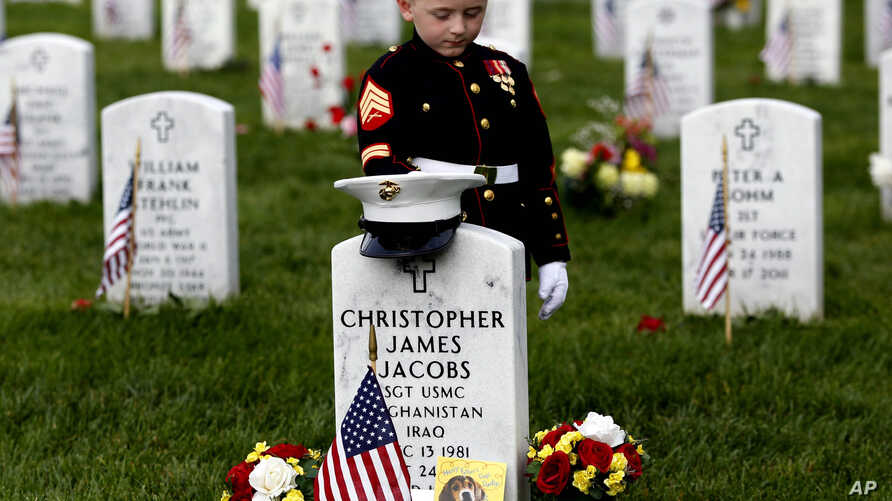 Christian Jacobs, 5, of Hertford, N.C., dressed as a Marine, pauses at his father's gravestone on Memorial Day at Arlington National Cemetery in Arlington, Va., Monday, May 30, 2016.
