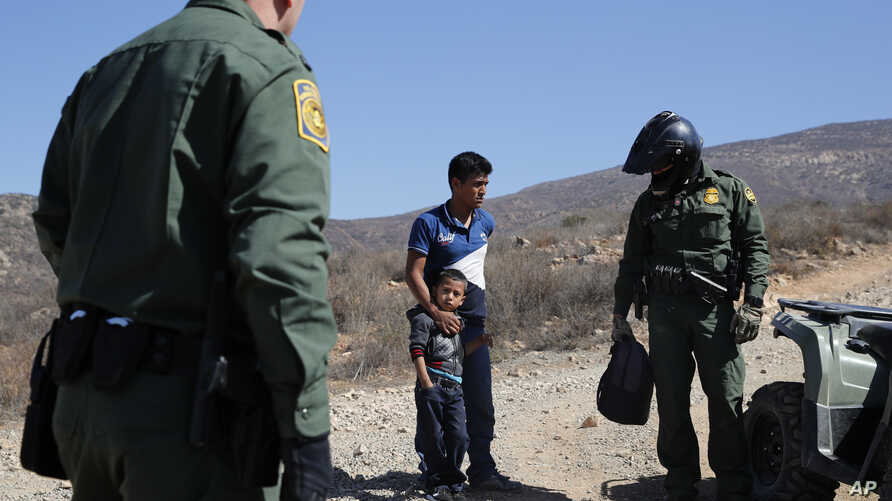 A Guatemalan father and son, who crossed the U.S.-Mexico border illegally, are apprehended by U.S. Border Patrol agents, June 28, 2018, in San Diego, California..