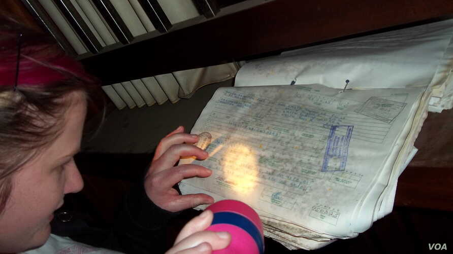 """A GPS member pores over old documents during a probe of an abandoned hospital near Johannesburg where they recorded a very loud noise """"like a man that took in his breath. We have no logical explanation for that sound."""" (Photo Courtesy the Gauteng Par"""