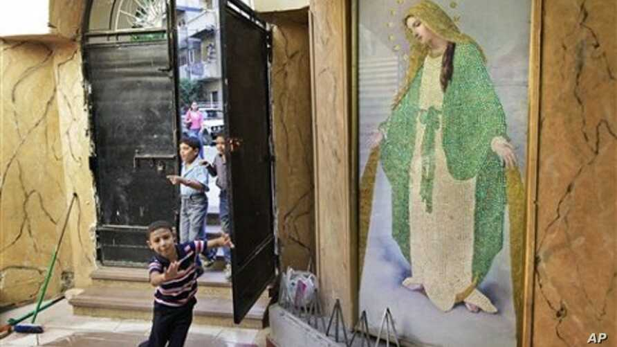 Children run past a painting of Mariam Al-Adra (Virgin Mary) inside the entrance of the Virgin Mary Coptic church in the al-Asafra area of the coastal city of Alexandria, Egypt (July 2010 file photo)