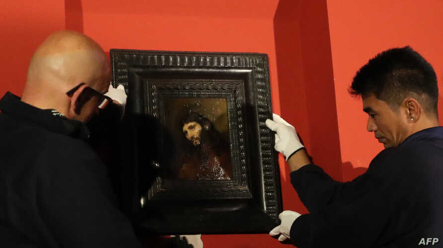 "People hang a paining entitled ""Study of the head and clasped hands of a young man as Christ in prayer,"" oil on oak panel, by Dutch painter Rembrandt on display at the Louvre Abu Dhabi, in the Emirati capital, Feb. 9, 2019."