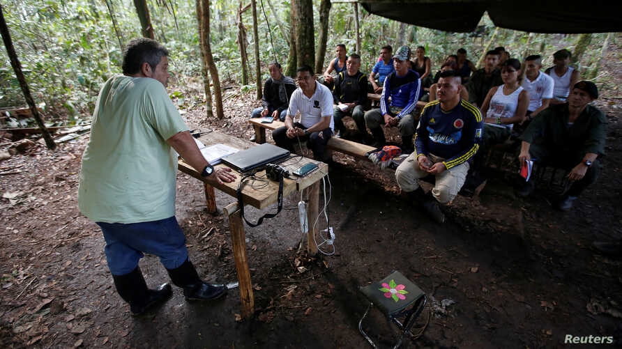 Marco Leon Calarca, (L) a member of the Revolutionary Armed Forces of Colombia (FARC), talks to members of FARC, at a camp to prepare for an upcoming congress ratifying a peace deal with the government, near El Diamante in Yari Plains, Colombia, Sept
