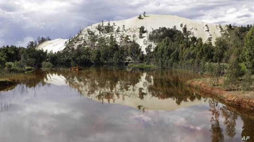 A gold mine dump is reflected in toxic water in Randfontein, west of Johannesburg, South Africa, January 26, 2011.