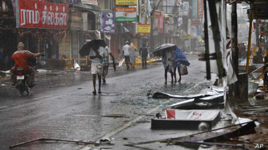 People walk past fallen sign boards and other trash caused by heavy winds in Pondicherry, India, December, 30, 2011.
