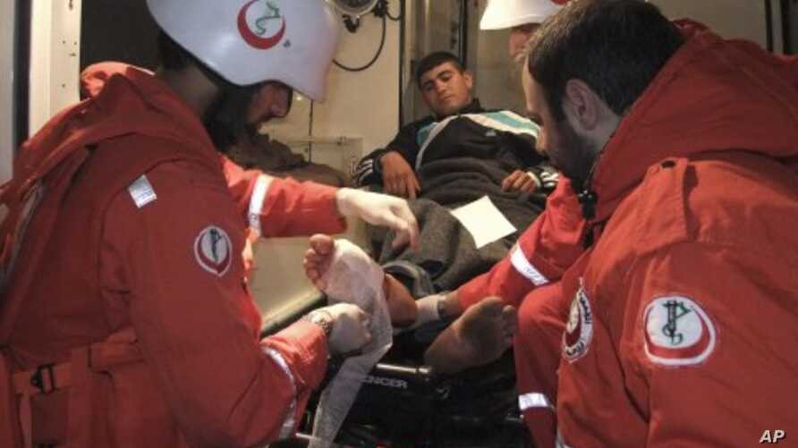 Lebanese medics treat an injured Syrian man before taking him to a hospital after he crossed from the Syrian town of Talkalakh into the northern border area of Wadi Khaled, Lebanon, May 14, 2011