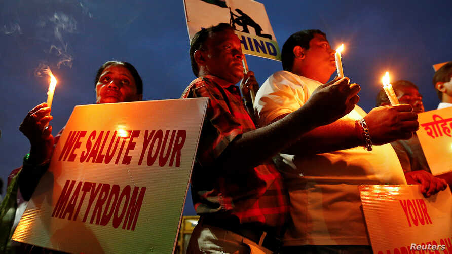 People hold candles and placards during a vigil for the soldiers who were killed after gunmen attacked an Indian army base in Kashmir's Uri, Mumbai, India, Sept. 19, 2016.