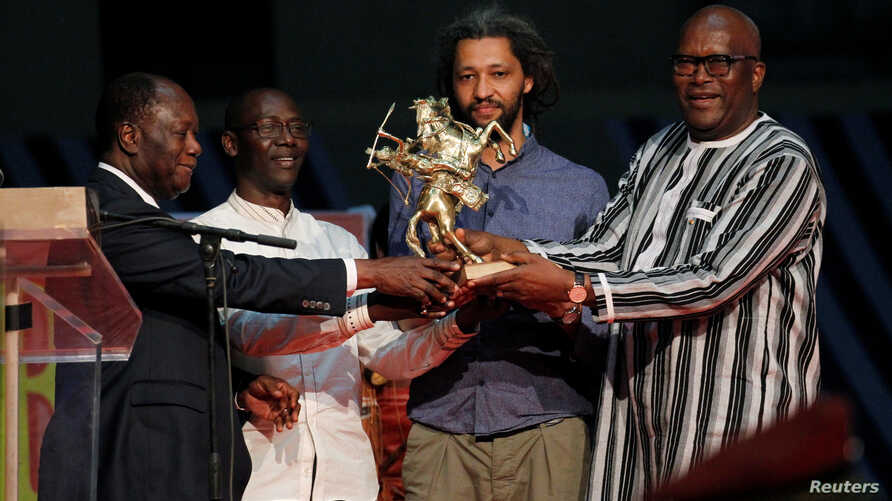 """The French-Senegalese Alain Gomis (2nd R), director of the movie """"Felicite,"""" receives the Etalon d'Or de Yennenga from Burkina Faso's President Roch Marc Christian Kabore (R) and Ivory Coast's president Alassane Ouattara (L) during  the FESPACO film"""