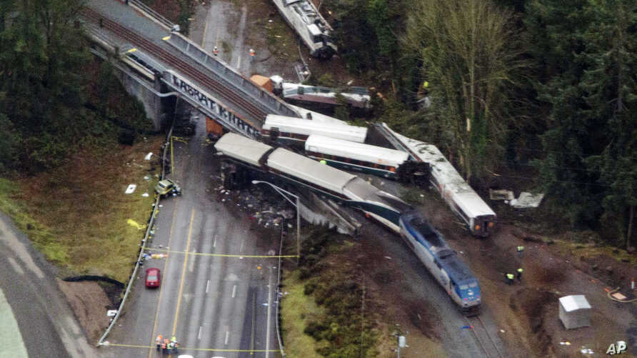 Cars from an Amtrak train that derailed above lie spilled onto Interstate 5, Dec. 18, 2017, in DuPont, Wash.