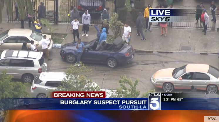 Suspects and bystanders are seen taking selfies after a two-hour car chase through Los Angeles Thursday in this screengrab from KTLA TV.