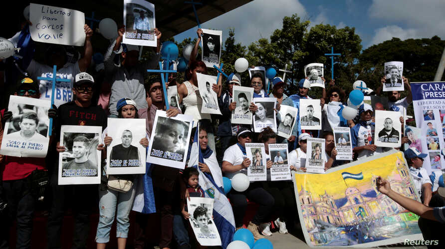 """Nicaraguan expats living in Costa Rica hold pictures of people killed in riots or imprisoned as they take part in the """"Caravan for Liberty and Justice"""" to protest against the government of Nicaraguan President Daniel Ortega, in La Cruz, Costa Rica, o"""
