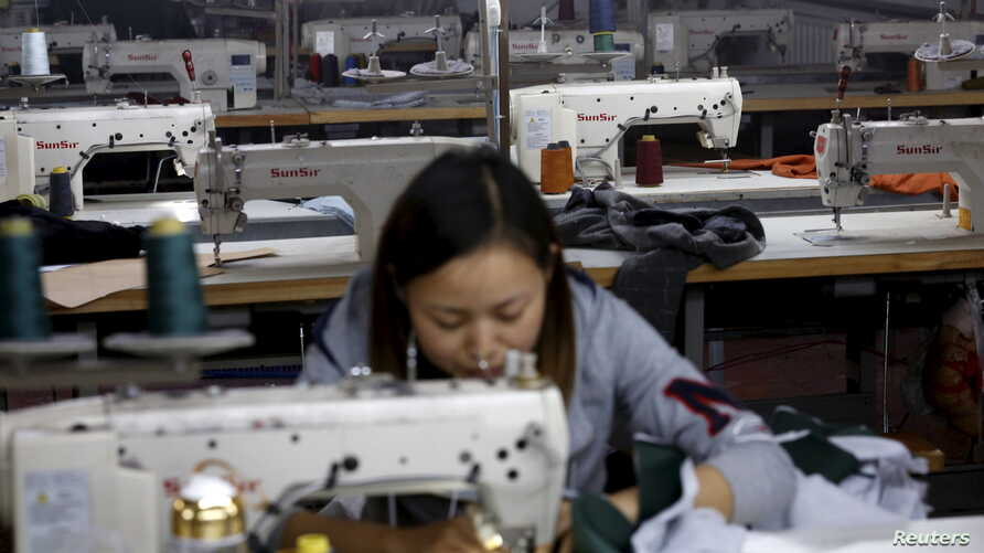 FILE - A woman works in a small-sized factory producing clothes and hats, in which more than half of its production line has stopped its operation because of a downturn in its business at the Qingyundian industrial zone in Beijing, Oct. 19, 2015.