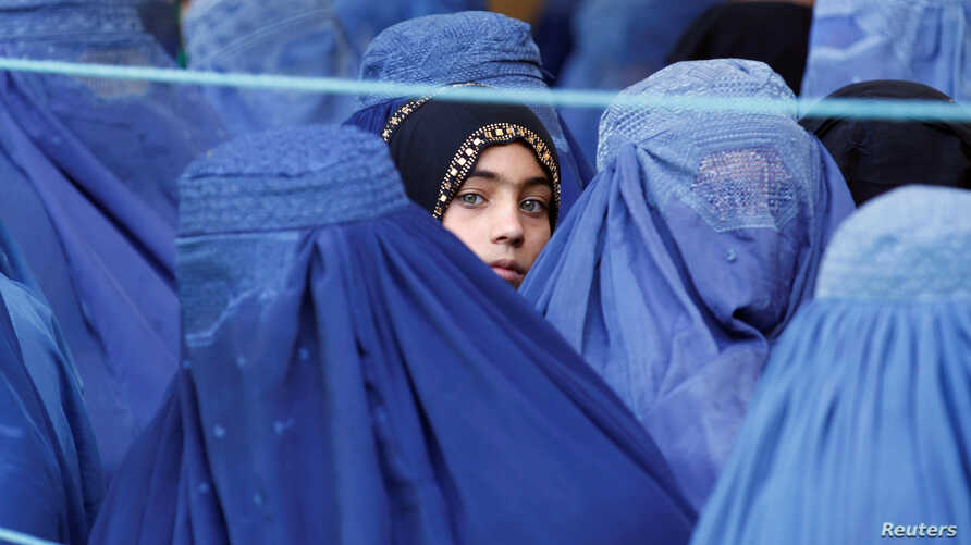 A girl looks on among Afghan women lining up to receive relief assistance in Jalalabad, Afghanistan, June 11, 2017.  In Afghanistan, openly using a woman's name is taboo, but a social media campaign is starting to challenge that.