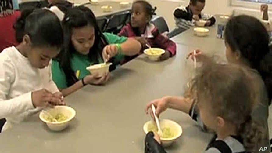 Students in the Kids Cafe after-school program learn about the nutritious value of an avocado while making an avocado and bean dip.