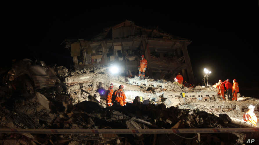 Rescue workers work to save people trapped under debris after an earthquake in Ercis, near the eastern Turkish city of Van, October 25, 2011.