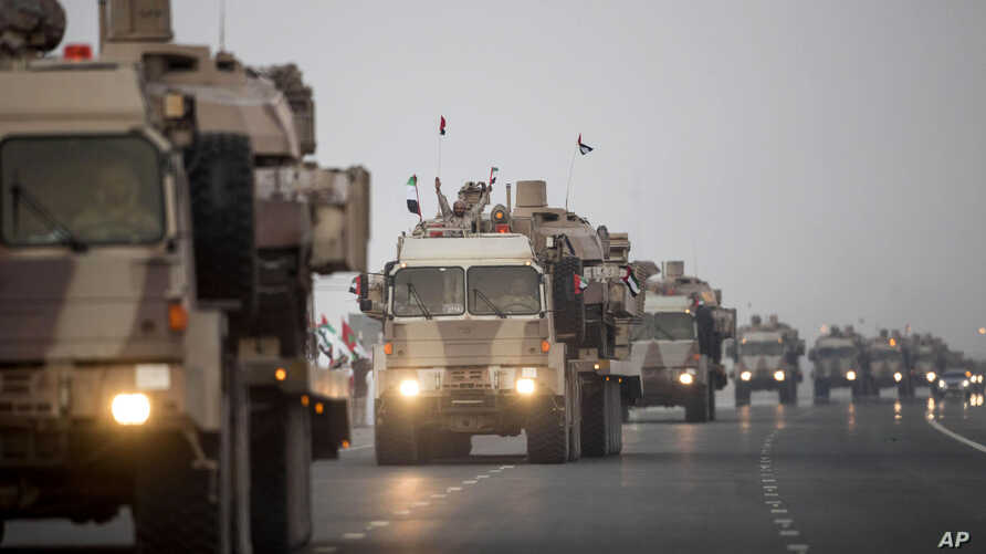 In this photo from the Emirates News Agency, WAM, UAE military vehicles and personnel travel from Al Hamra Military Base to Zayed Military City, an Emerati base, marking the return of the first batch of UAE Armed Forces military personnel from Yemen,