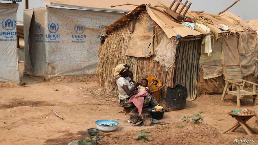 FILE - A woman takes care of her child in a camp sheltering internally displaced people (IDPs) next to the M'Poko international airport in Bangui, Central African Republic, Feb. 13, 2016.